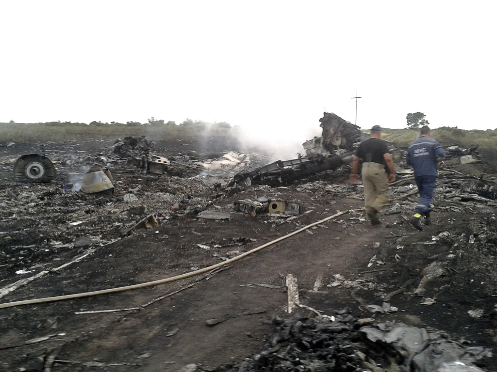 Emergencies Ministry members examine the wreckage of a Malaysia Airlines Boeing 777 plane that crashed in the settlement of Grabovo in the Donetsk region of eastern Ukraine on Thursday. An emergency services rescue worker said debris was spread across an area up to about 9 miles in diameter.