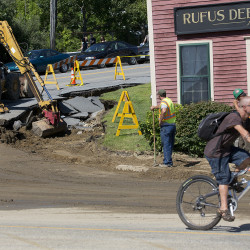 A cyclist passes by while utility workers begin repairing road damage near Rufus Deering Lumber on Commercial Street in Portland.
