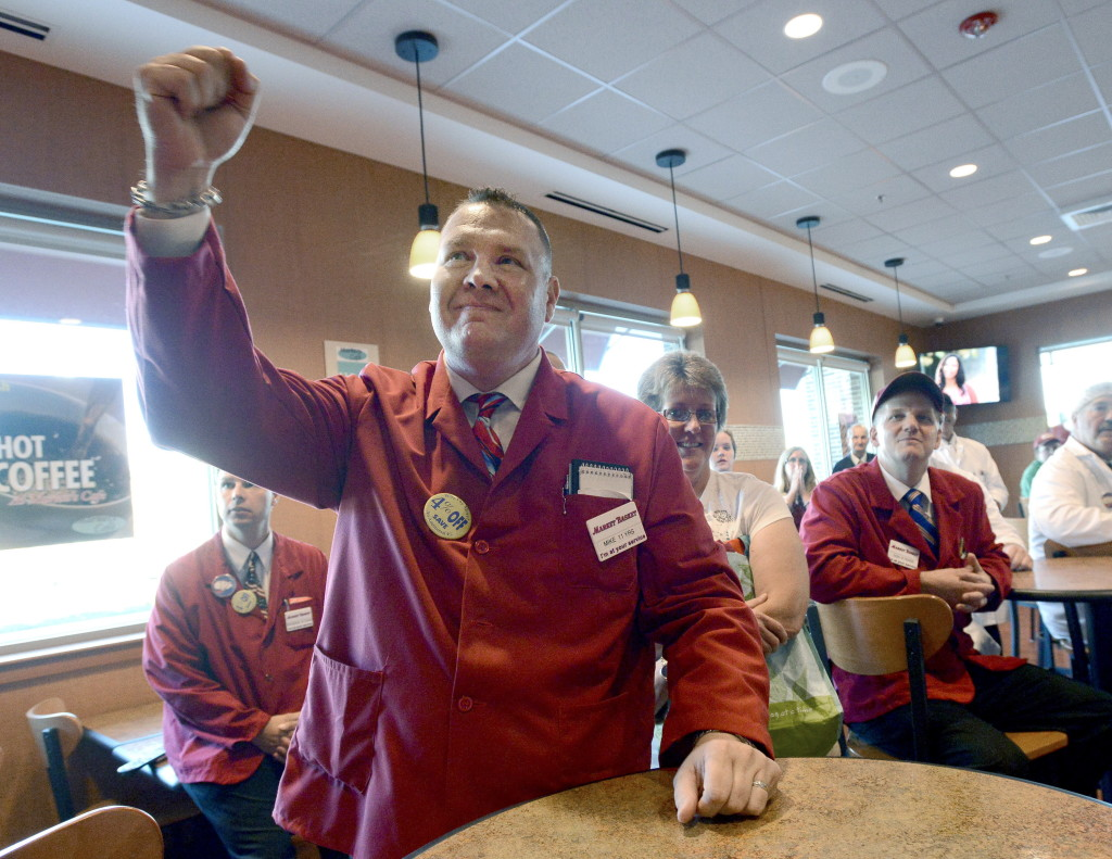Front-end manager Mike Menard pumps his fist as he and store employees gather in their lunchroom at the Market Basket in Biddeford to watch on a television as Arthur T. Demoulas holds a news conference.