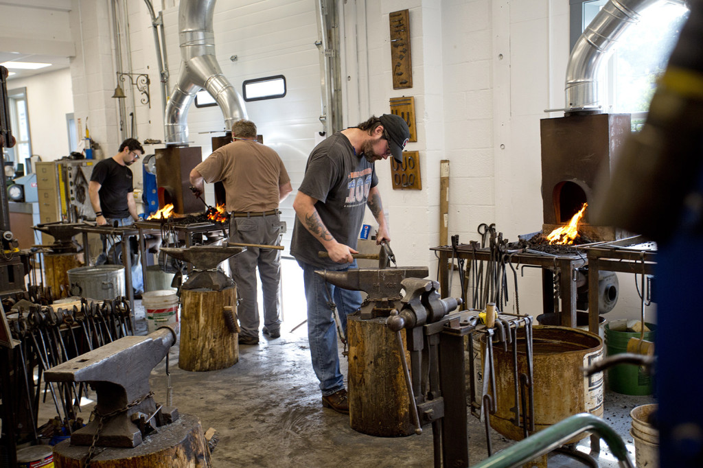 Students including, left to right, Alexander Bazes, of Westchester, N.Y., Tom Johnson of Kittery Point, and Shawn Kelly of Phippsburg, take part in a blacksmithing class.