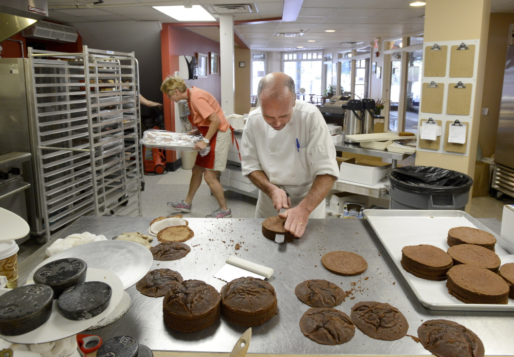 Ed Foley makes chocolate mousse cakes as Molly Foley places a tray into a rack at their bakery in Monument Square in Portland. They have sold their bakery business to baker Andrea Swanson.