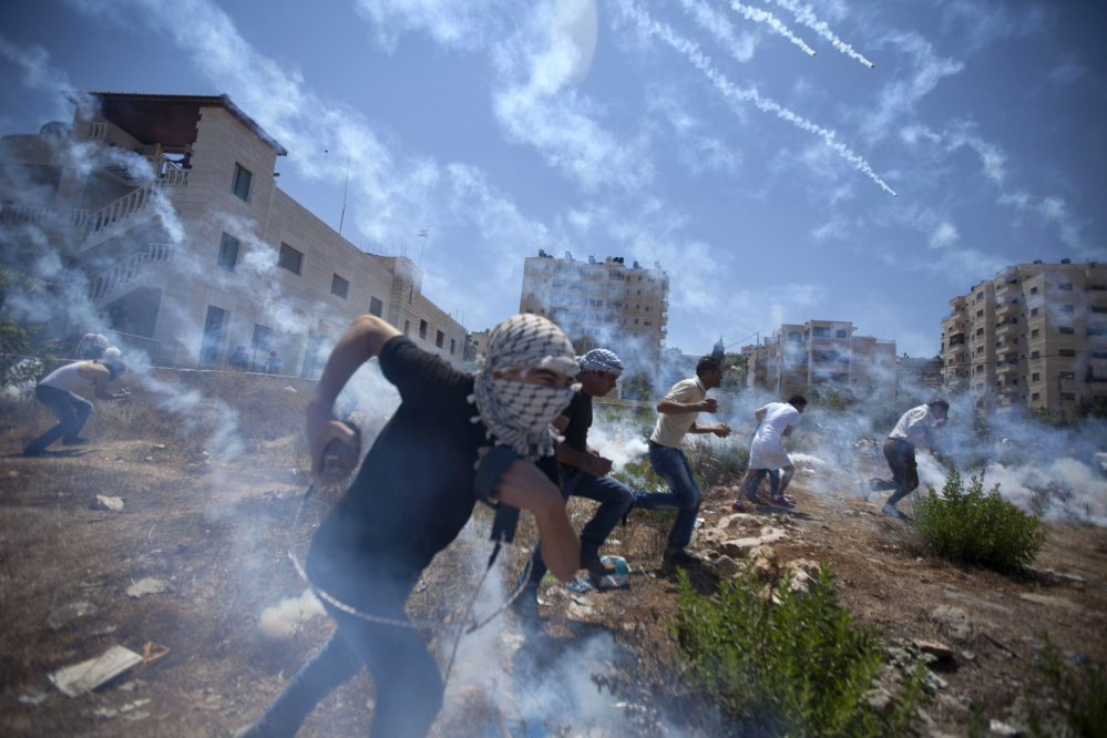 Palestinians run for cover during clashes with Israeli soldiers following a protest against the war in the Gaza Strip, outside Ofer, an Israeli military prison near the West Bank city of Ramallah, on Friday.
