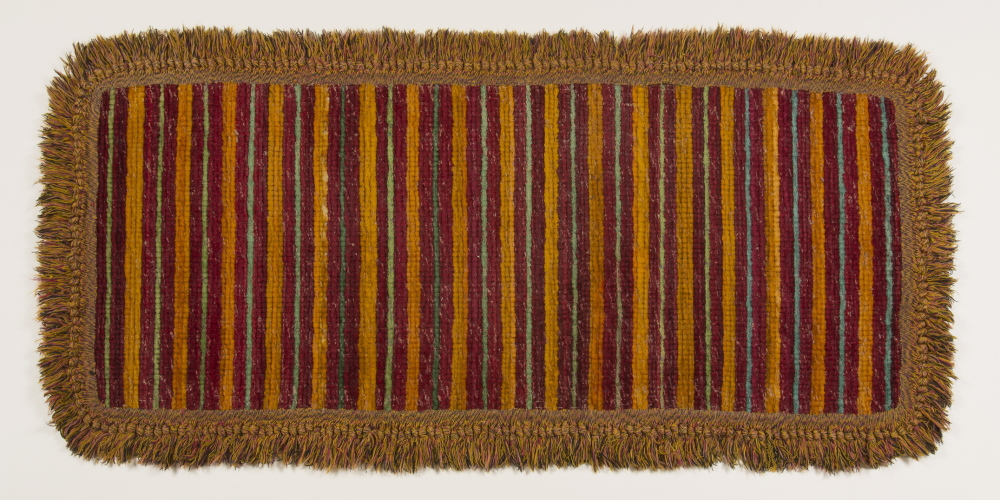 "A woven plush rag rug with ""peacock fringe"" border, 1890, made by Sister Ada S. Cummings of the Sabbathday Lake Shaker community. A Shaker woven plush rag rug from 1890."