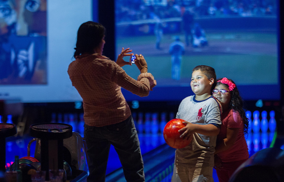 Jacqueline Martinez takes a picture of her son Ryan, 6, and daughter Isabel, 4, as they bowl at Lucky Strike in Chicago.