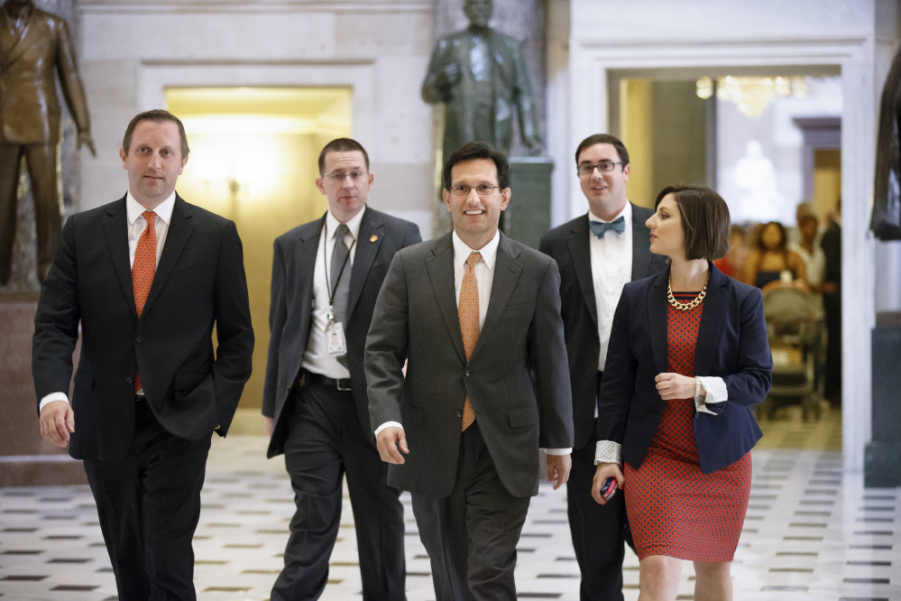 The Associated Press Rep. Eric Cantor, R-Va., surrounded by his staff as he walks to the House chamber Wednesday, gave up his leadership post Thursday, then announced Friday that he will leave Congress on Aug. 18.