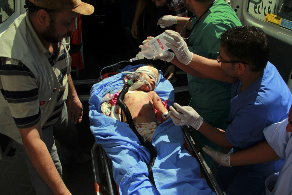 Medics treat a Palestinian child wounded in shelling in Rafah, southern Gaza Strip on Saturday. Israel bombarded Rafah on Saturday as troops searched for an officer they believe was captured by Hamas in an ambush that shattered a humanitarian cease-fire and set the stage for a major escalation of the 26-day-old war.