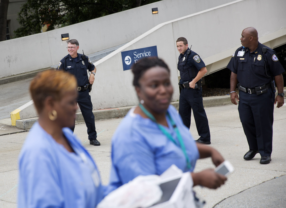 Hospital workers pass police officers guarding an entrance to Emory University Hospital.