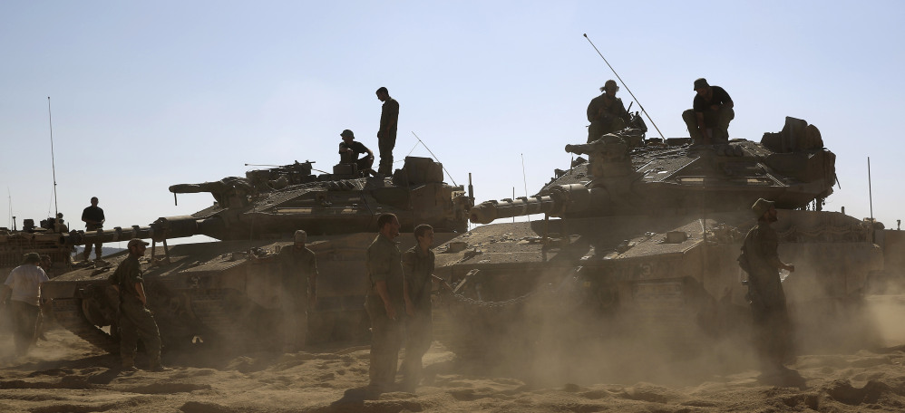 Israeli soldiers gather near the border with Gaza on Saturday. The conflict has killed about 1,700 Palestinians, mostly civilians, 63 Israeli troops and three Israeli civilians.