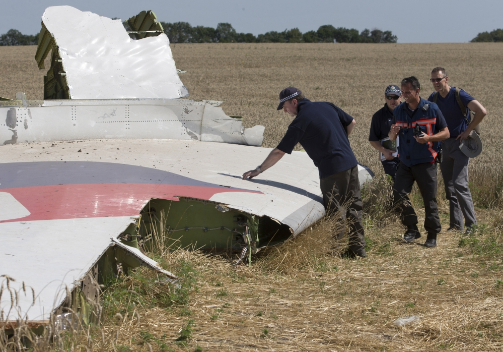 Investigators examine wreckage of the Malaysia Airlines jet near Hrabove, Donetsk region, eastern Ukraine, on Friday.