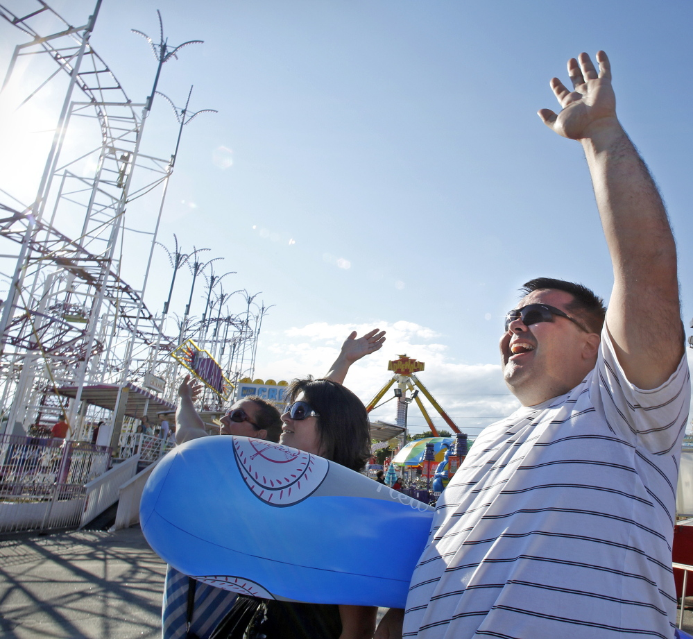 Michael Fecteau of Coaticook, Quebec, waves to a family member on a ride at Palace Playland in Old Orchard Beach. He said he's been visiting the town almost every summer since he was a child. Amelia Kunhardt/Staff Photographer