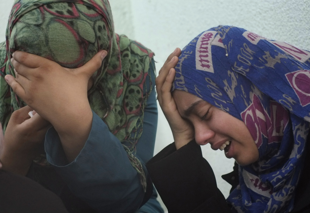 Palestinian relatives of the Abu Wahdan family cry outside the morgue of the Kamal Adwan hospital in Beit Lahiya after the bodies of three members of the family, that were killed in an overnight Israeli strike, were taken away for their funeral on Sunday. Jamila, 55, Hatem, 57, and Sanwara Abu Wahdan , 27, were killed at the hit, after the extended family of more than 40 people had sought refuge in Jebaliya from shelling elsewhere.