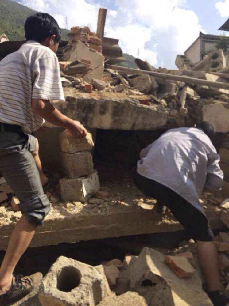 In this cellphone photo released by China's Xinhua News Agency, men scramble amid the rubble of buildings as they look for survivors after an earthquake in Ludian on Sunday.
