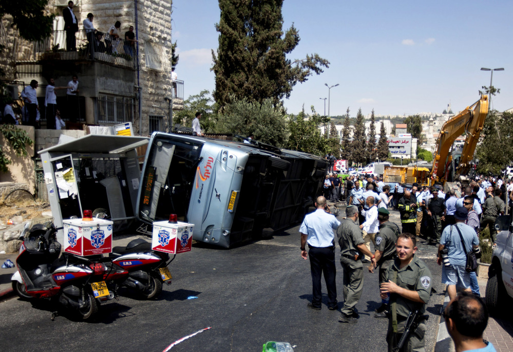 Israelis stand near a flipped bus at the scene of an attack in Jerusalem, Monday.