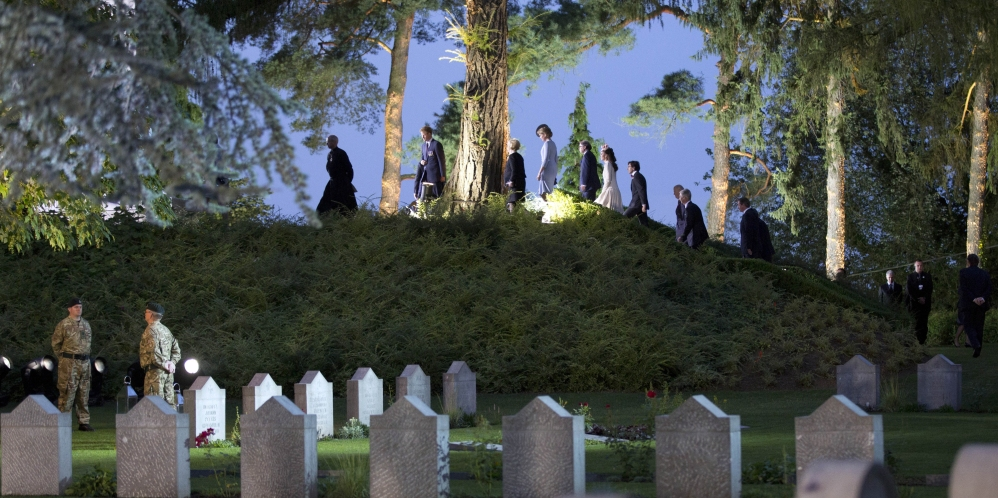 Heads of state and others walk up to the top of a hill to lay flowers during the ceremony Monday at the Saint-Symphorien cemetery in Belgium.