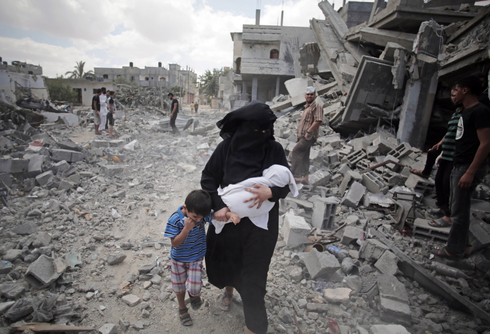 A Palestinian woman leads a boy past people inspecting the rubble of destroyed houses following Israeli strikes in Rafah refugee camp in the southern Gaza Strip on Monday. A pause in hostilities elsewhere did not apply to Rafah.