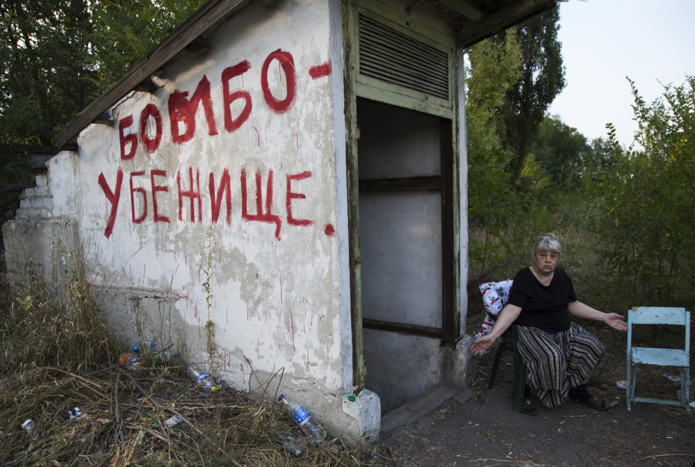 "Local resident Galina Dudkina gestures near to an entrance with ""Bomb Shelter"" written on the side, as she waits for shelling to start in Petrovsky district in the city of Donetsk, eastern Ukraine, Monday."