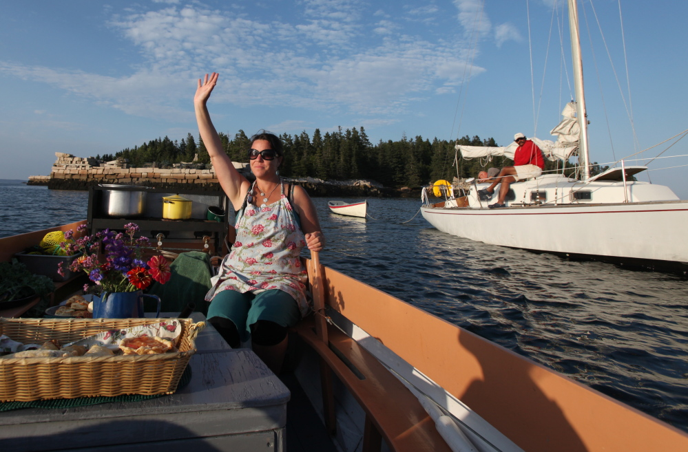 Reilly Harvey waves as she guides her boat Mainstay around the harbor between Dix Island and High Island.