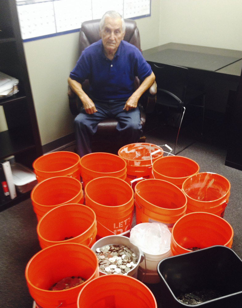 Andres Carrasco sits in his Los Angeles office with buckets of change totaling more than $20,000 that he received as a partial settlement in his suit against an insurance company.