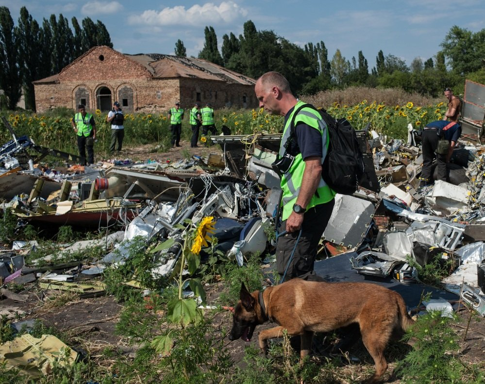 Australian, Malaysian and Dutch investigators examine the site of the downed Malaysian jet Tuesday near the village of Rossipne, Donetsk region, eastern Ukraine.