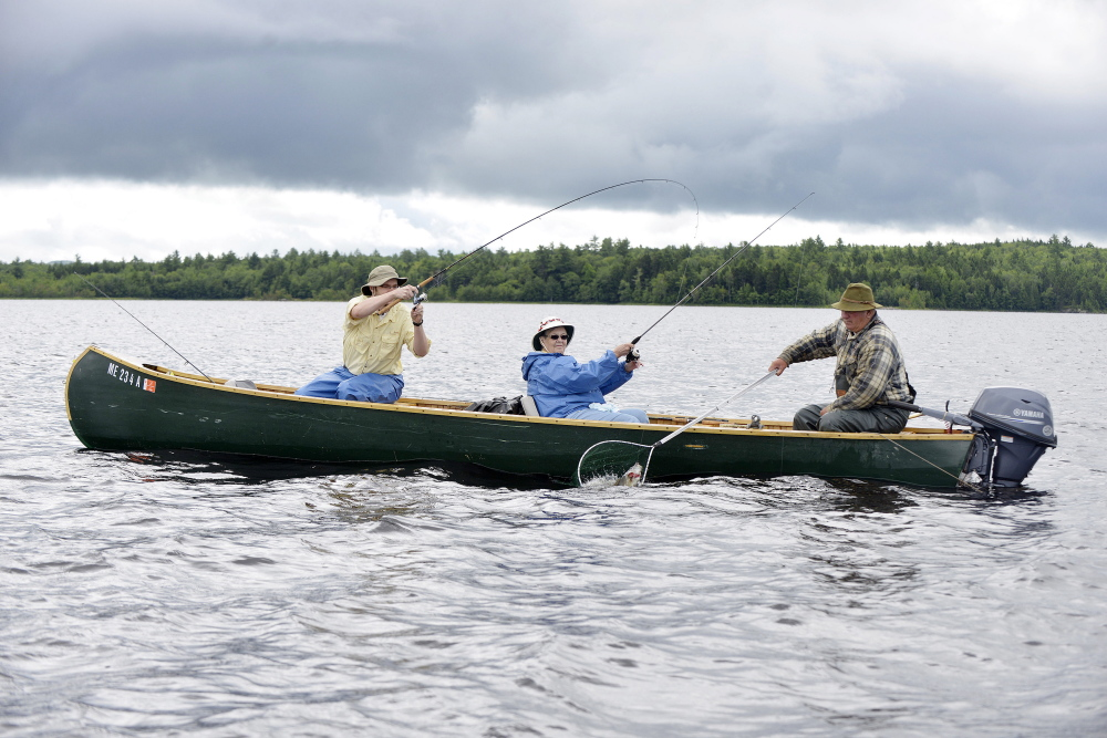 Maine guide Lance Wheaton nets a bass for client Phil Kadzielawski while fishing on Baskahegan Lake with his grandmother, Mary Anne Kadzielawski.