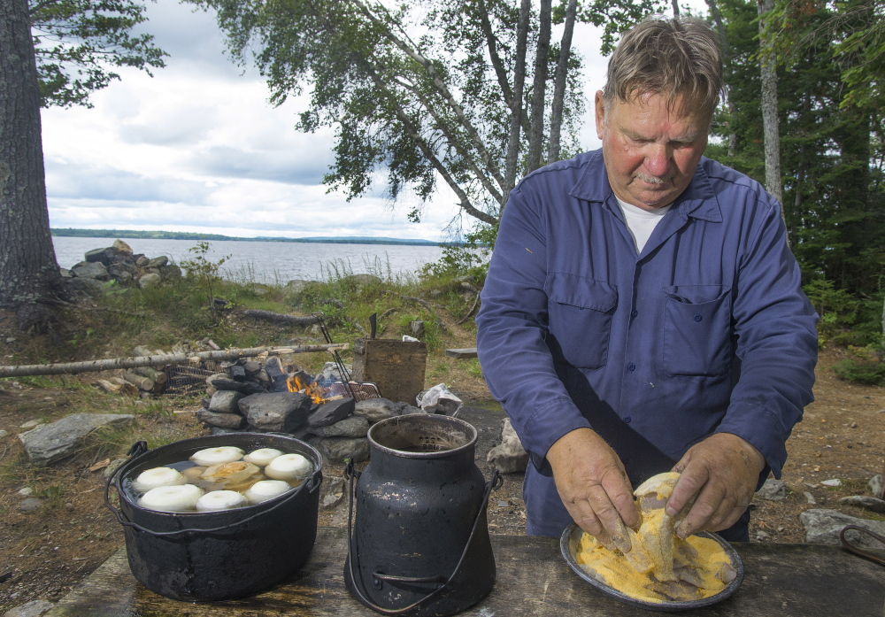 Maine guide Lance Wheaton coats the now-cleaned fish fillets in cornmeal while preparing a traditional shore lunch for his clients.