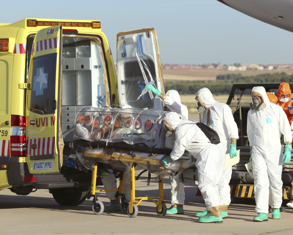 Aid workers and doctors transfer Miguel Pajares, a Spanish priest who was infected with the Ebola virus while working in Liberia, from a plane to an ambulance. Photo provided by the Spanish Defense Ministry.