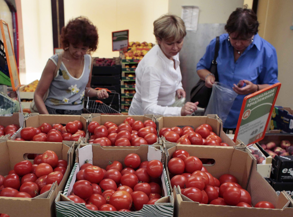 Women choose Dutch tomatoes at a supermarket in downtown Moscow on Thursday. The Russian government's food ban aims to hurt Europe, Canada, the U.S. and Australia.