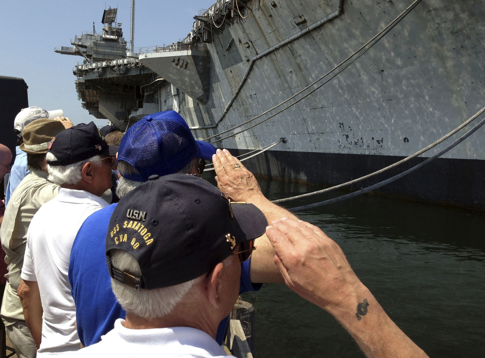 Veterans of the decommissioned aircraft carrier USS Saratoga salute the vessel during a farewell ceremony Friday at Naval Station Newport in Rhode Island.