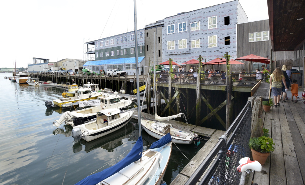 A building under construction on Maine Wharf in Portland will house a new restaurant and offices. Casco Bay Lines terminal is on the left and Flatbread restaurant is on the right.