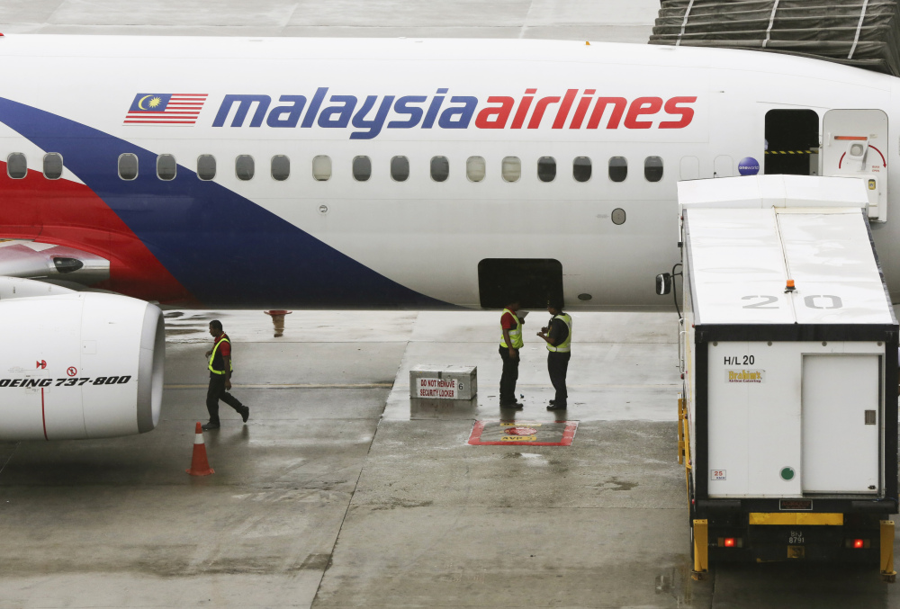Ground crew members stand near a Malaysia Airlines aircraft at the Kuala Lumpur International Airport in Sepang, Malaysia, last May. Malaysia's state investment company said Friday that it plans to remove struggling Malaysia Airlines from the stock exchange, making it fully state-owned.