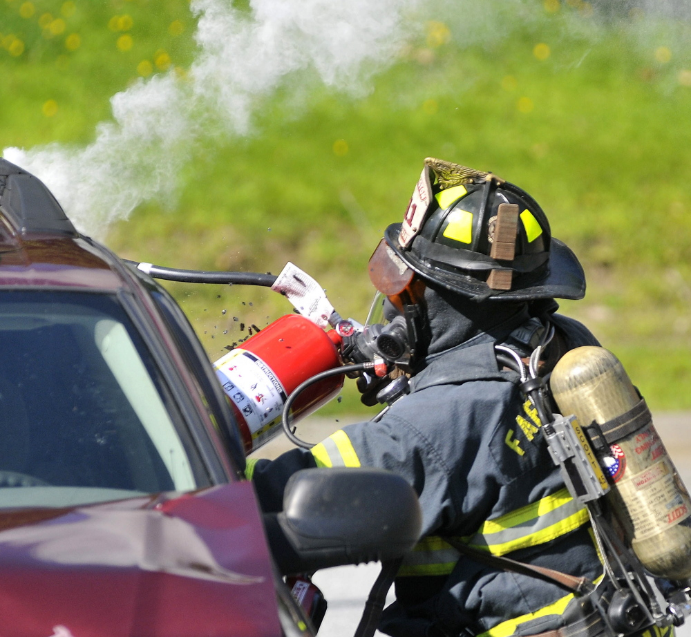 A Farmington firefighter breaks a vehicle's window during the Homeland Security training exercise Friday.