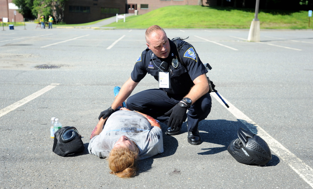 Darin Gilbert, Farmington police officer, tends to  a person portraying a car bombing victim in the parking lot at the University of Maine at Farmington during a Homeland Security training event Friday.