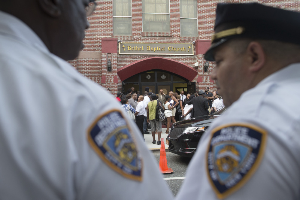 New York City police officers stand at their post as mourners arrive for the funeral service of Eric Garner at Bethel Baptist Church in Brooklyn last month.