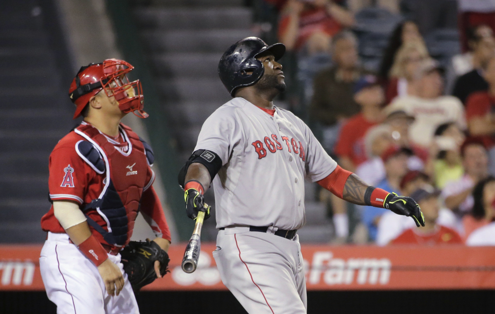 Boston Red Sox's David Ortiz, center, and Los Angeles Angels catcher Hank Conger watch the flight of Ortiz's sacrifice fly that scored Dustin Pedroia during the 14th inning of a baseball game on Saturday in Anaheim, Calif.
