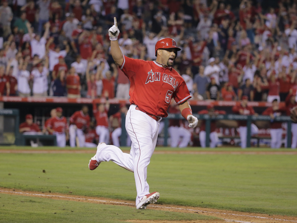 Los Angeles Angels' Albert Pujols celebrates his walk-off home run during the 19th inning of a baseball game against the Boston Red Sox on Sunday, in Anaheim, Calif. The Angels won 5-4.