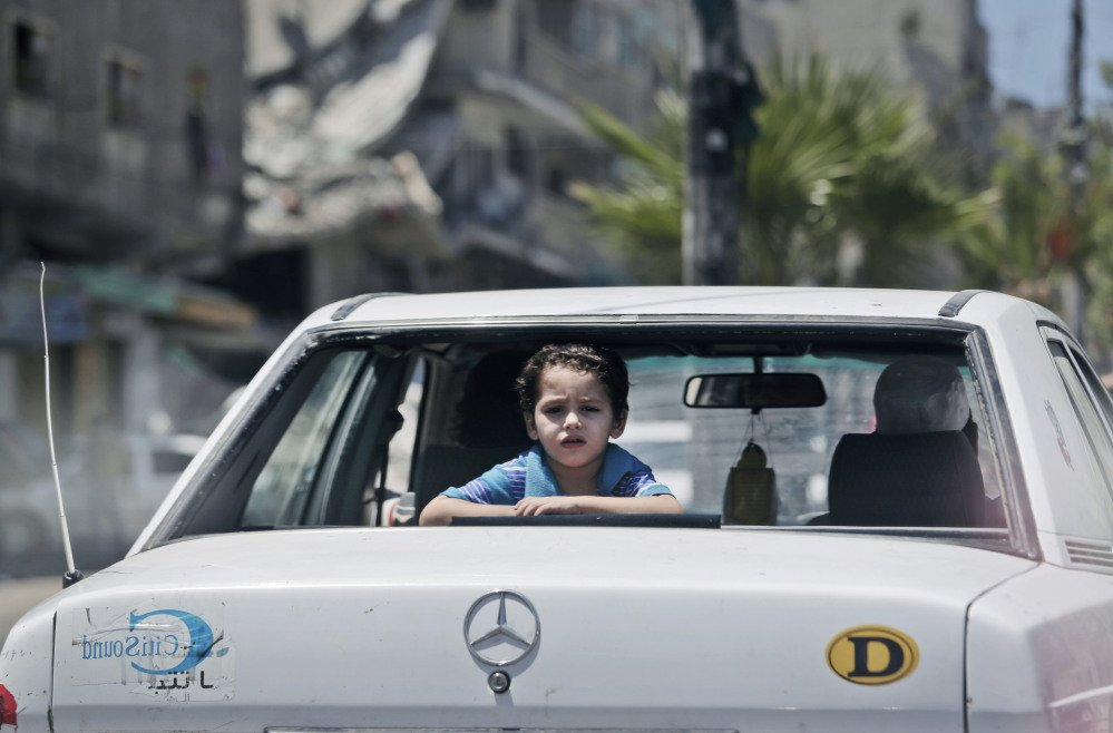 A Palestinian boy looks outside a car, back dropped, by the rubble of a house hit by an Israeli strike during the Gaza war, in Gaza City, Sunday.