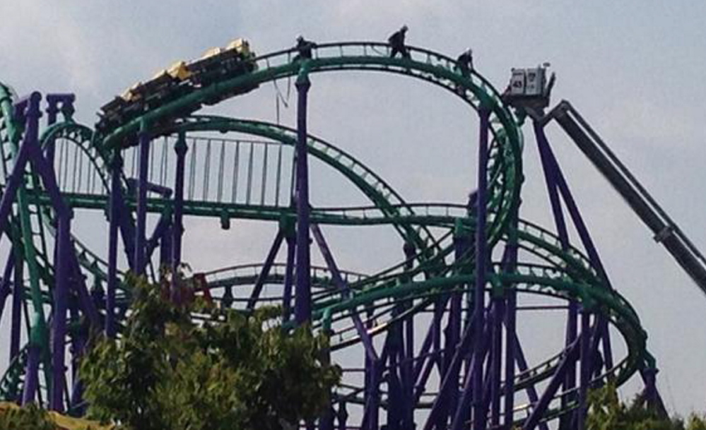 Firefighters reach riders stranded on The Joker's Jinx roller coaster at Six Flags America in Upper Marlboro, Maryland on Sunday.