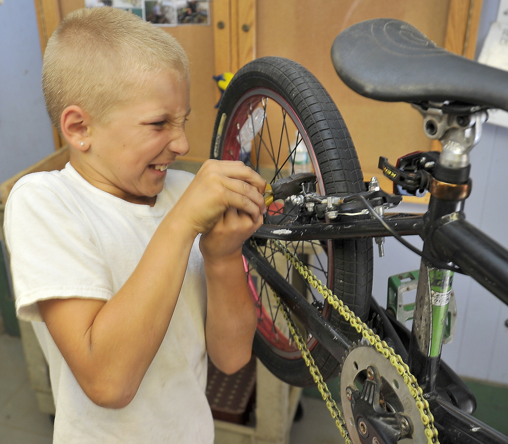 Austin Cantara, 10, pulls hard on a wrench as he tightens a nut on the brake pad that he just replaced on his bike at the Community Bicycle Center, a nonprofit program in Biddeford.