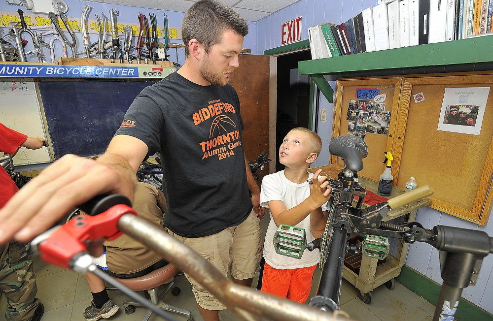 Austin Cantara, 10, gets help replacing the brake pads on his bicycle from volunteer and program director Andrew Burnell  at the Community Bicycle Center. Gordon Chibroski/Staff Photographer