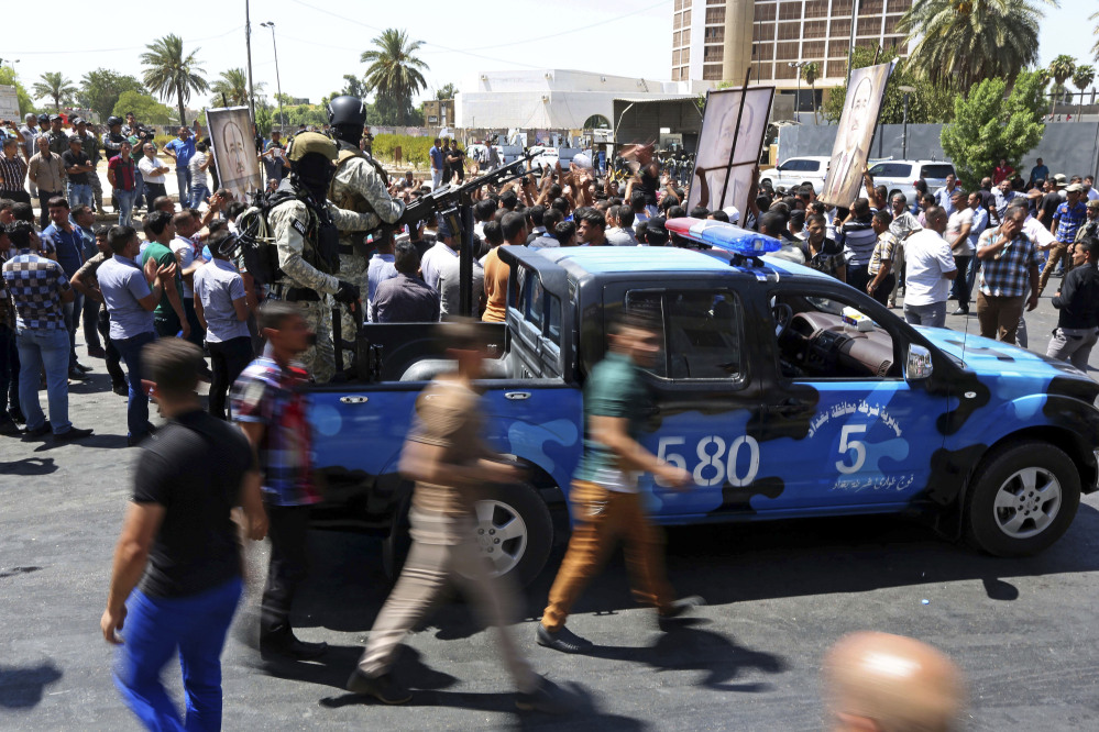 Iraqi security forces stand guard amid tight security by Iraqi security forces that sealed off roads around a pro-government demonstration supporting Embattled Prime Minister Nouri al-Maliki,  Iraq, Monday.