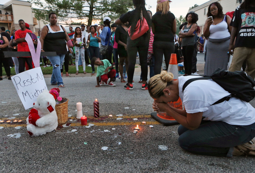 Meghan O'Donnell, 29, from St. Louis, prays at the spot where Michael Brown was killed, Sunday evening, in Ferguson, Mo.