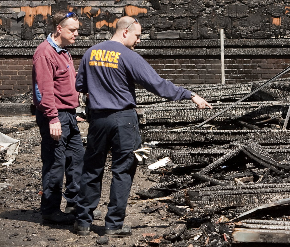 Investigators comb through the rubble of a Lewiston fire that started May 3, 2013. The fire destroyed four apartment buildings on Bartlett and Pierce streets.