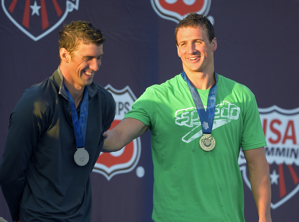 Ryan Lockte, right, jokes around with Michael Phelps during the medals ceremony in the men's 200-meter individual medley final at the U.S. nationals of swimming, Sunday, in Irvine, Calif.