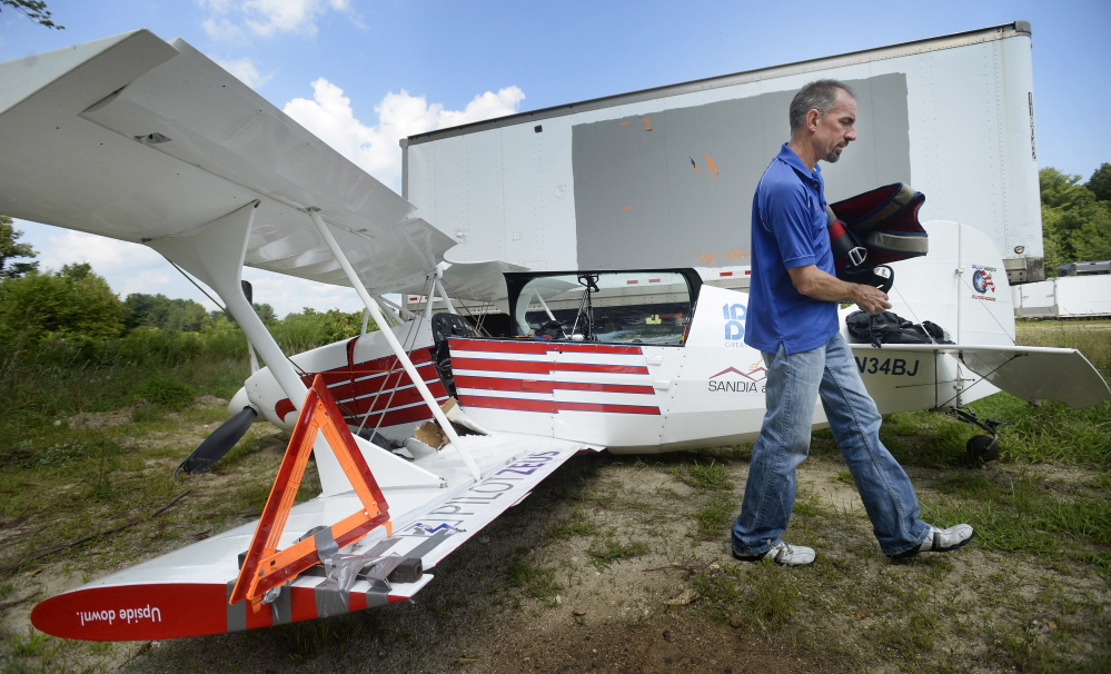 "Billy Werth removes belongings from his single-engine experimental aircraft Monday at Copp Motors in Cumberland, where the wreckage was towed after he crash-landed Sunday in Standish. ""I'm just happy to be here,"" said Werth, whose injuries were minor."