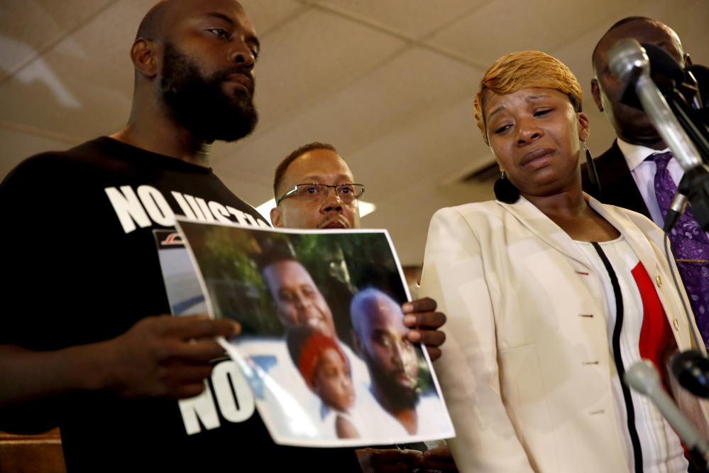 Lesley McSpadden, right, the mother of 18-year-old Michael Brown, watches as Brown's father, Michael Brown Sr., holds up a family picture of himself, his son, top left in photo, and a young child during a news conference Monday, in Ferguson, Mo.