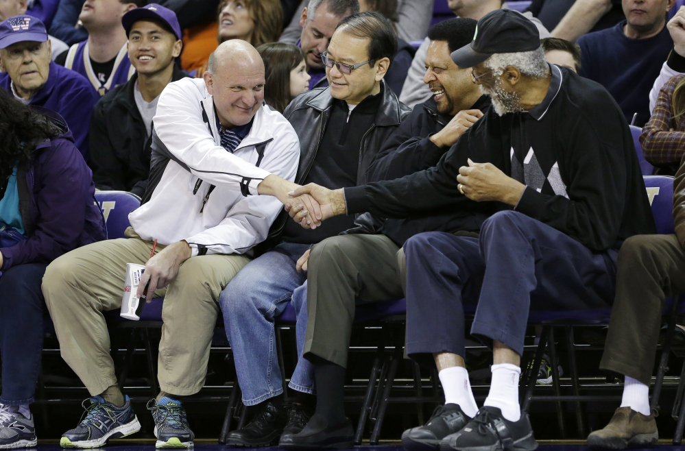 "In this Jan. 25, 2014, photo, then-Microsoft CEO Steve Ballmer, left, shakes hands with former NBA players Bill Russell, right, and ""Downtown"" Freddie Brown as Omar Lee looks on during an NCAA college basketball game between Washington and Oregon State in Seattle."