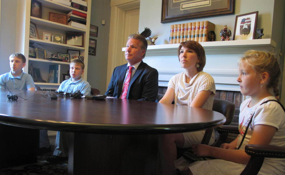 The wife and children of Jeffrey Fowle sit with their attorney, Tim Tepe, center, during a news conference Tuesday.
