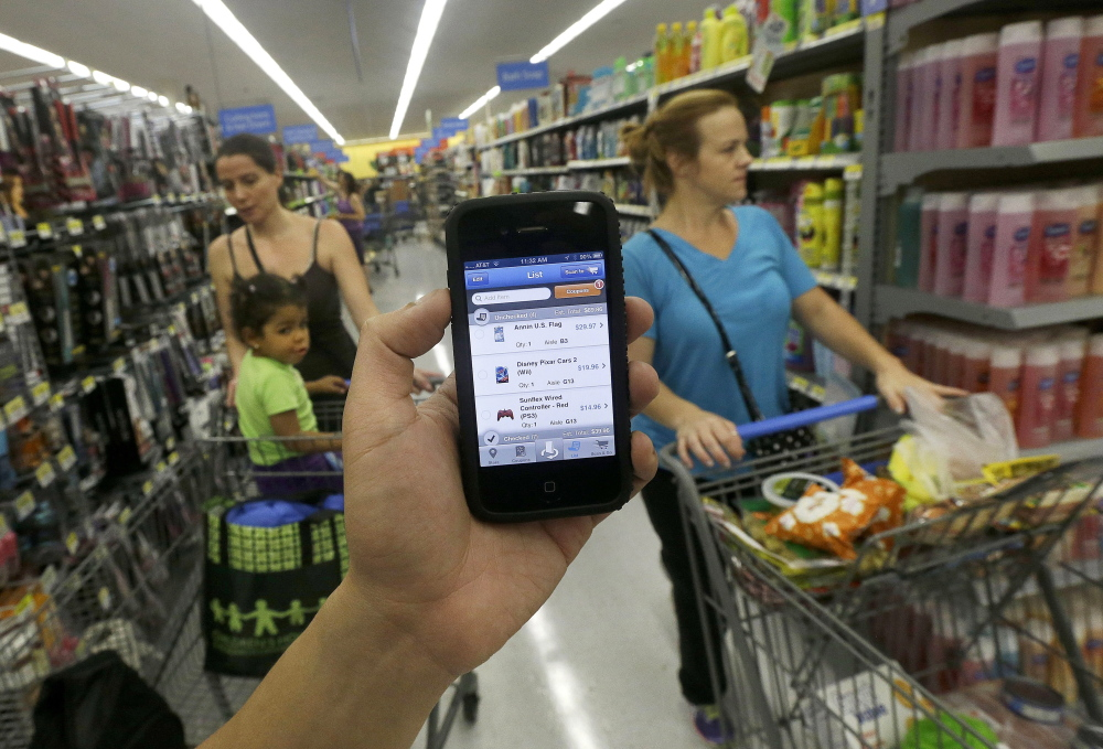 A Wal-Mart representative demonstrates the now-discontinued Scan & Go mobile application last September at a Wal-Mart in San Jose, Calif. Instead of looking at the app as a failure, Wal-Mart took what it learned from Scan & Go to create another service: It found that customers like being able to track their spending before checking out.