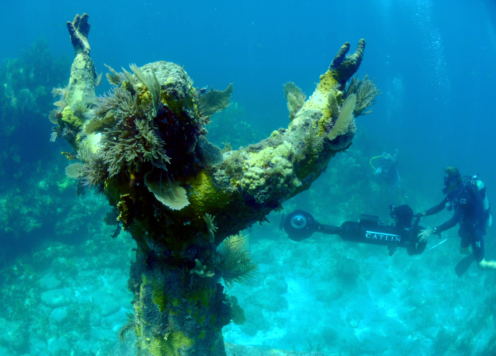 "In this Aug, 6, 2014 photo provided by Catlin Seaview Survey, Catlin's Christophe Bailhache surveys ""Christ of the Abyss,"" with the SVII cameras off the coast of Key Largo, Fla."