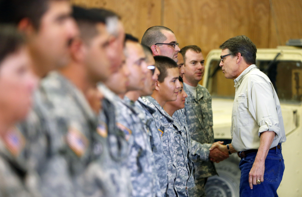 Gov. Rick Perry shakes hands with National Guard troops training at Camp Swift in Bastrop, Texas, on Wednesday.